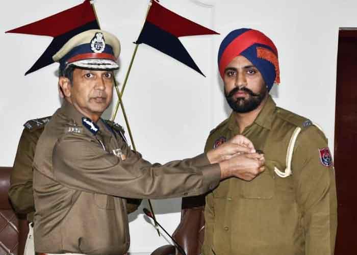 Dinkar Gupta giving medal to Police Personnel