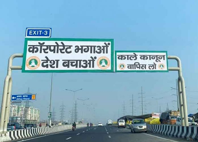 Farmers affix black laws banners on NH signboard